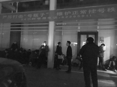 """门诊大楼左侧特需挂号处有十几名号贩子在排队,上方挂着""""打击号贩子""""的横幅。"""