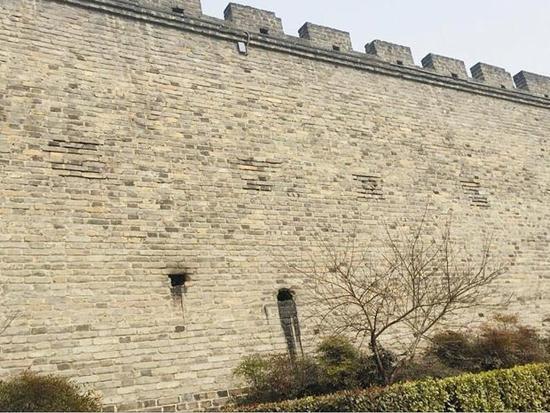 图为:襄阳城墙被餐馆运营户凿墙开洞排油污