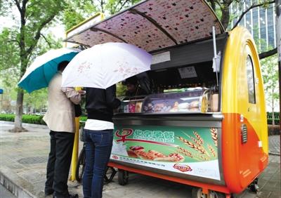 2011年4月21日,东城区东直门内大巷,市民在早饭车前买早饭。材料图像
