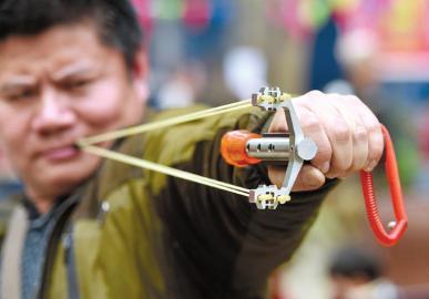 右手不太方便的杨先生使用的弹弓是特制的。