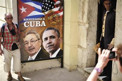 3月19日,古巴首都哈瓦那,在奥巴马和劳尔卡斯特罗的宣传画旁边,一名游客在摆姿势与其合影。图/CFP
