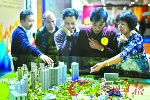 市民在沙盘前了解楼盘情况(资料图片)。 广州日报记者廖雪明 摄
