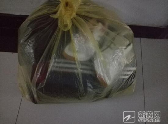 分娩室门口,产妇的队服和鞋子被一只花色的塑料袋包着。