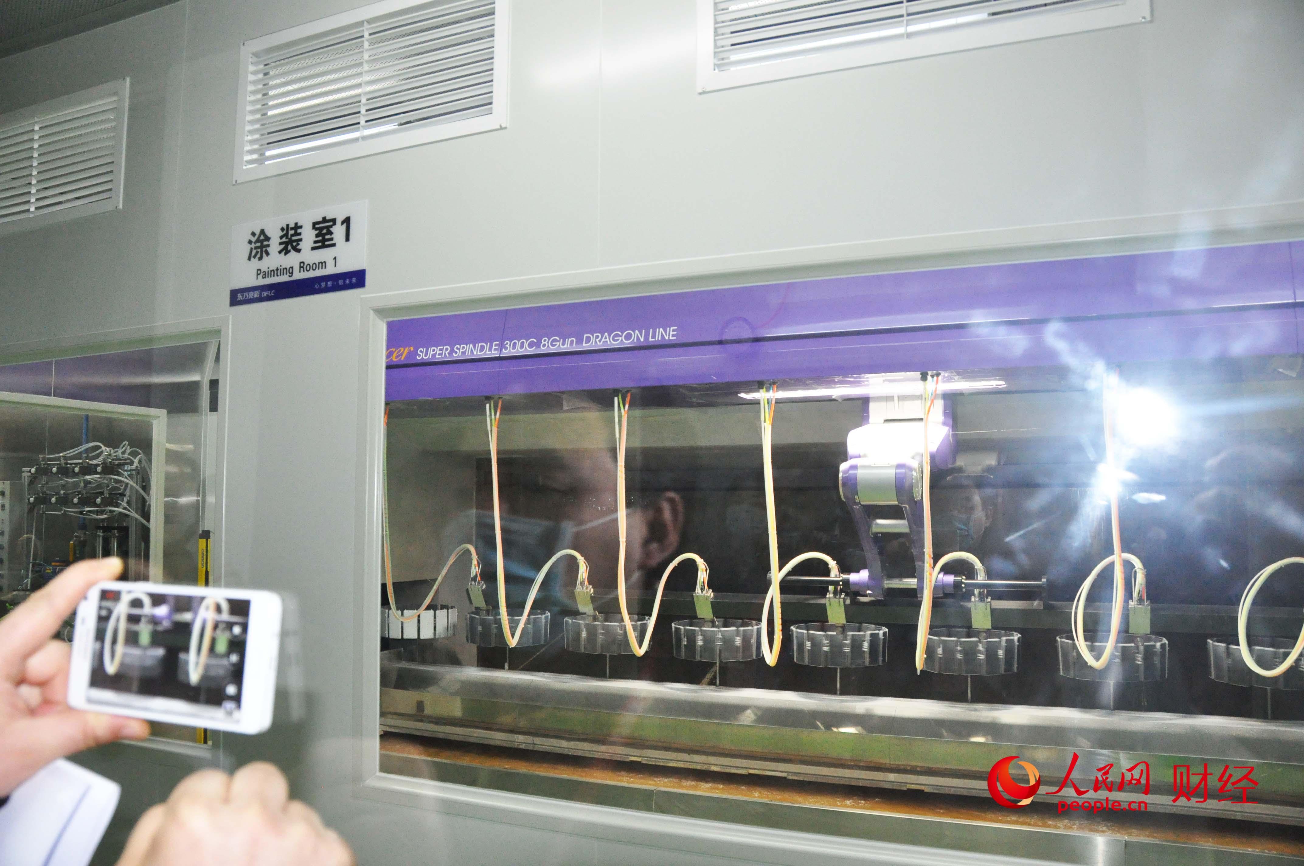 东莞横沥镇,东方亮彩模具厂的智能车间,智能设备正在给手机外壳上涂料。(人民网 贾兴鹏摄)