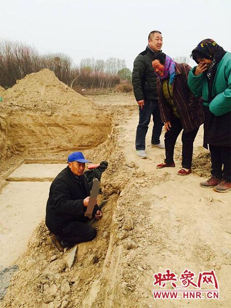 徐某从被挖开的坟墓中捡拾亲人的尸骨。