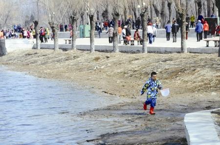 24日,一名男孩在二一九公园开化后的湖边挖土玩乐 ...