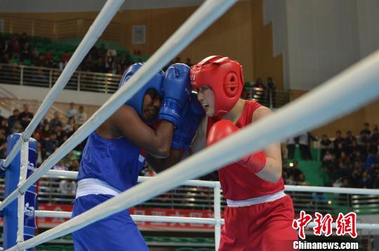 图为朝鲜选手李同顺(红)对战印度尼西亚选手克里斯蒂娜.马瓦.美贝(蓝)。 韩冰 摄