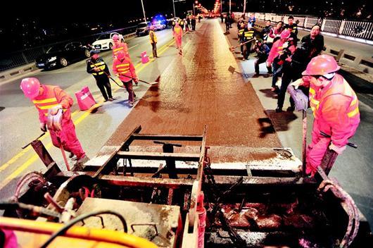 楚天都市报讯 图为:昨日凌晨,工人给长江大桥铺上国内最新型的路面精表材料。 楚天都市报记者李辉摄