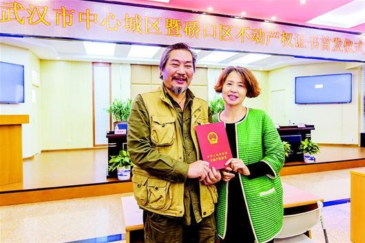 """湖北日报讯 昨日上午,在武汉市�~口区政务服务中心,李伟桥、林丽清夫妇领到自家房子的不动产权证书。</p><p>  """"随后挂断了电话。</p><p>   袁晶 摄<img src="""
