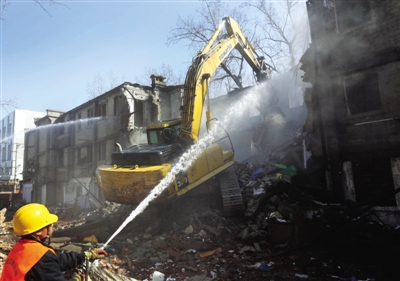 昨日,拆楼机对楼体进行拆除,工作人员朝着楼体表面喷水减少扬尘。