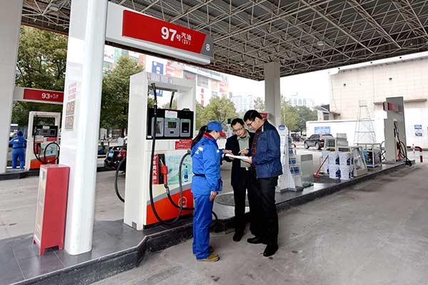 调查人员在当地加油站向工作人员了解情况。