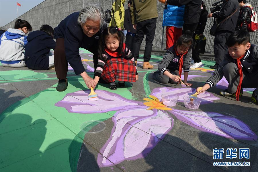 """3月28日,南京大屠杀幸存者伍秀英(前左一)与小学生志愿者一起用美术颜料手绘紫金草图案。当日,""""紫金草手绘行动""""在侵华日军南京大屠杀遇难同胞纪念馆雕塑广场举行,南京艺术学院的画家和来自社会各界的200名志愿者一起,用美术颜料手绘紫金草图案,将和平之花""""种植""""在纪念馆雕塑广场的地面上。新华社记者韩瑜庆摄"""