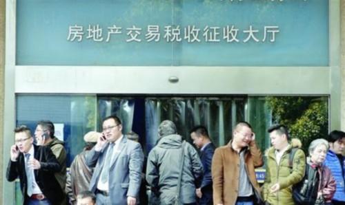 新政落地后,上海闵行房地产交易中心大门口聚集着前来办理业务的市民。 /新华社