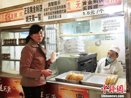 """前来买饼的老顾客满玉梅还不知道眼前这位讲信用、好说话的小老板是个残疾人。""""他每天很辛苦,做事踏实。""""不善言辞的满玉梅忍不住为他点赞,我们都要向他学习。 徐雪 摄"""