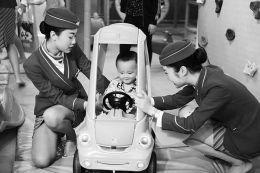 """3月29日,南航乘务人员陪自闭症孩子玩游戏。世界自闭症日临近,南航乘务人员走进海口雨润特殊教育培训学校,开展""""蓝丝带""""自闭症儿童关爱主题活动,为孩子们送上爱心。"""