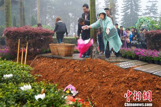 图为逝者家属将鲜花抛入花坛内。 黄威铭 摄