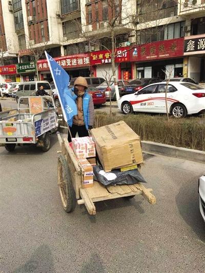 3月10日,河南省郑州市,因电动三轮车禁行,部分快递使用板车运送货物。图/CFP