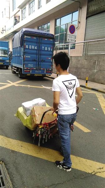 昨日,深圳东门迎宾馆停车场旁。因为车被扣,面包车进不了小巷子,只能拖运送货。读者供图