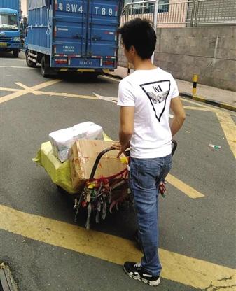 昨日,深圳东门迎宾馆停车场旁。因为车被扣,面包车进不了小巷子,只能拖运送货。