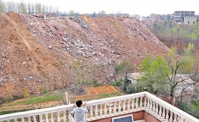 垃圾山下的村民担心一旦下大雨,院子会被淹。
