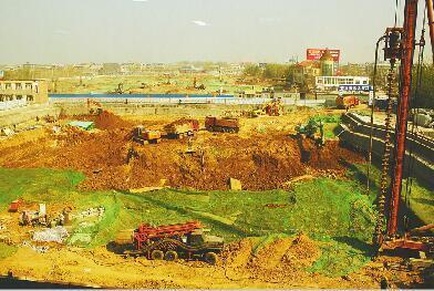 3月31日上午,该工地内仍有渣土车不断出入、大面积裸露。 (潘庆照 摄)