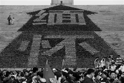 """伴随清明节的到来,全国各地各界人士纷纷举办多种形式的凭吊活动,祭奠、缅怀先烈。3月30日,南京雨花台烈士陵园的烈士纪念碑前布置了由数万盆鲜花组成的""""缅怀""""花坛,吸引众多市民游客。泱波摄"""