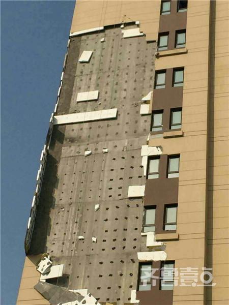 """""""一场大风,刮出来个楼纸纸!""""1日,济南世贸原山首府的不少业主发现:小区4号楼5-11层的保温墙大面积掉落,原因竟是前一夜五级大风吹刮所致!这不禁让人质疑开发商的工程质量。对此,开发商山东世盈置业有限公司工作人员称:保温板掉落是施工队修整外墙时所致,""""保温板被切割摘除,切口空隙容易兜风,恰遇大风,才导致外墙脱落""""。"""