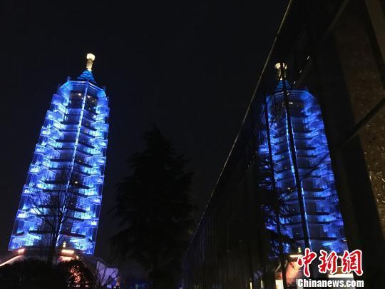 """在第九个世界自闭症意识日(WAAD)前夕,南京大报恩寺塔""""变身""""闪烁蓝光的""""琉璃塔"""",为所有自闭症儿童点亮一盏爱的""""蓝灯""""。 申冉 摄"""