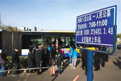 昨日,八宝山地铁站附近,人们排队乘坐公交摆渡车前往八宝山公墓。新京报记者 尹亚飞 摄