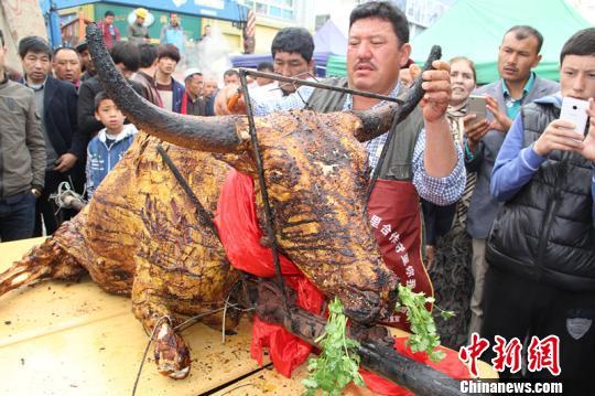 2日,新疆烧烤巨匠莫明?吾甫尔再次展现其烧烤特技,在伊宁县举行的第七届新疆伊犁杏花旅行节上烤制出一头约250千克重的牦牛,此前他烤牦牛的国际纪录是客岁创下的288千克。 朱景朝 摄