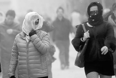 2日,路人纷纷戴上口罩或纱巾前行。 记者王锋 摄