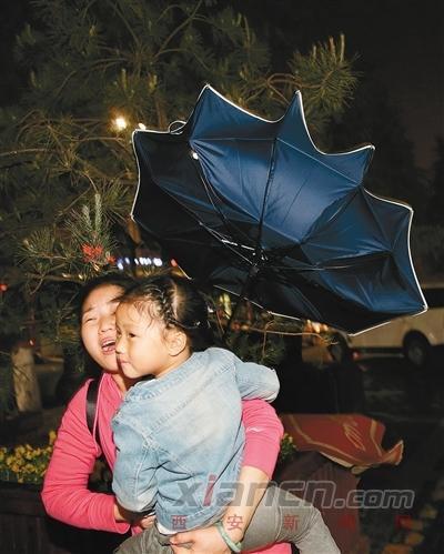 昨晚9时许,我市一阵风雨交加,路上的行人,有的雨伞被吹成喇叭花,有的临时拿着袋子顶在头上避雨,有的冒雨前行。 记者尚洪涛 摄