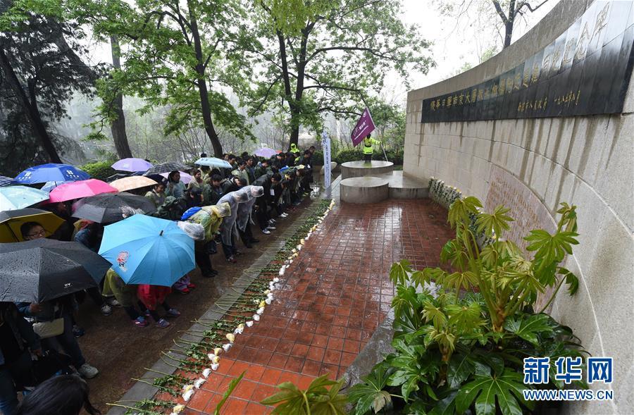 """4月2日,参加活动的市民从侵华日军南京大屠杀遇难同胞纪念馆出发。当日,江苏南京举行以""""紫金草·祭忆""""为主题的市民走访南京大屠杀遇难同胞丛葬地、凭吊遇难同胞活动。主办单位从数千名报名者中随机选出400多名市民和学生组成健步走、骑行两支队伍,从侵华日军南京大屠杀遇难同胞纪念馆出发,冒雨步行约8.5公里、骑行约20公里,分别在沿途各处丛葬地的纪念碑前献花祭奠。新华社记者孙参摄"""