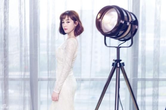 """张檬完美的驾驭了""""空气刘海"""",她身着紧身白色长裙一展姣好曲线,手持百合花束,简单的装扮更显春日活力,少女感十足。"""