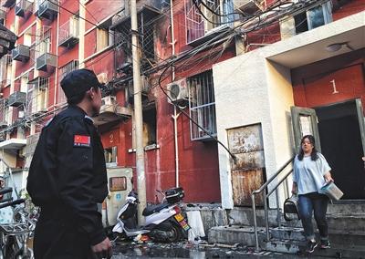 居民整理完家中的贵重物品后从居民楼走出。