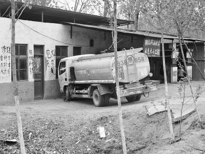 一辆油罐车正在给一处不法加油点送油