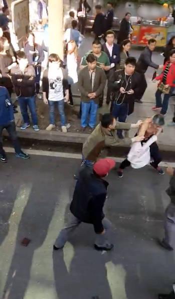 图为现场,男子和老人对打,捉住了老人的脖子,旁边很多路人围观。