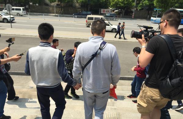 孙文麟和胡明亮在庭审结束后牵手走出法院