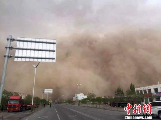"""4月15日下午,位于甘肃河西走廊最西真个酒泉市多地呈现沙尘气候。图为瓜州县呈现了宏大""""沙尘墙""""滔滔推动。 钟欣 摄"""