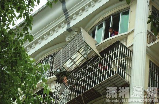 4月15日,长沙中南汽车全球G6栋,离开 墙体的护窗风雨飘摇。图/潇湘晨报记者陈斌