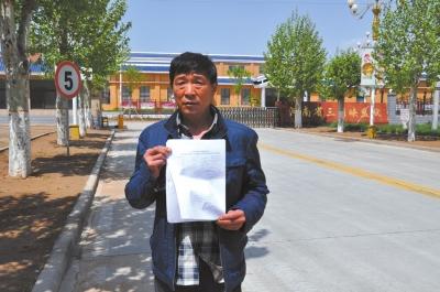 刘建国拿着检测报告在河南省三门峡监狱门口。