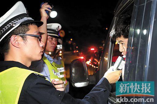 在广州市番禺区市桥一处查车点,执勤交警正对过往车辆的驾御员停止酒精度审查。 新快报记者 宁彪/摄
