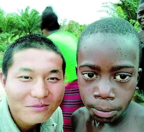 图为:刘明和安哥拉本地小男孩留影刘明和工