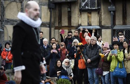 当地时间4月23日,游客在莎士比亚故乡、英格兰埃文河畔斯特拉福镇观赏艺术家为纪念莎士比亚逝世400周年而表演的戏剧。