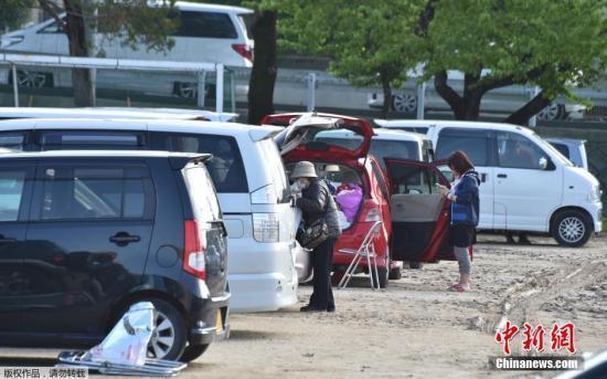 当地时间4月19日,日本熊本县益城町汇集众多地震避难者的停车场内,一家人在汽车内吃饭。