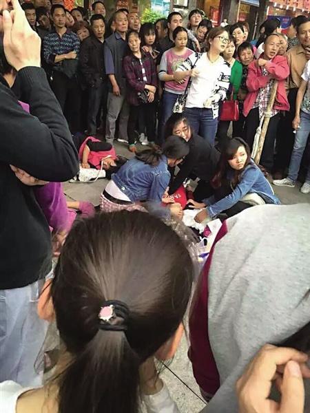 人和125路公交车站左近,4名女孩在对老太施救。 网友图