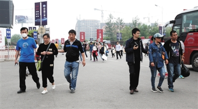 4月29日,新国展,四名便衣差人正将两名怀疑人带上警车。 本版拍照/新京报记者 尹亚飞