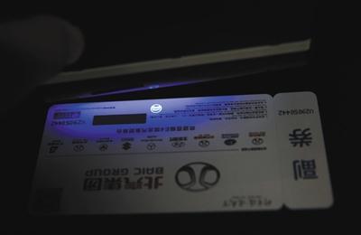 紫光灯照耀时,真门票下方会看到圆形亮色的防伪水印。