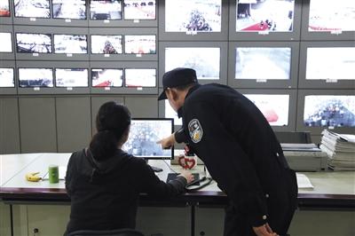 新国展监控室,一名民警正检察展区的监控画面。