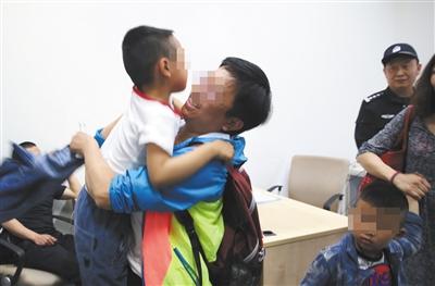 一名密斯抱起刚走散的儿子。此前,小伴侣被参展商的作业人员送到治安处置点。